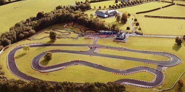 Une maison avec une piste de karting dans le jardin